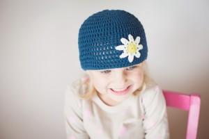 Schöne Häkelmütze in blau mit weißer Blume - bei ZWERGE.de